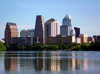 Skyline of Austin with a sculler rowing on Town Lake.